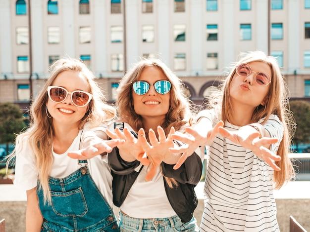 Ritratto di tre giovani belle ragazze sorridenti hipster in abiti estivi alla moda. donne spensierate sexy che posano per strada. modelle positive che si divertono in occhiali da sole. mostrano i loro palmi