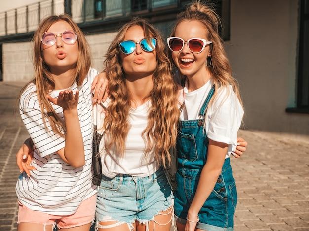 Ritratto di tre giovani belle ragazze sorridenti hipster in abiti estivi alla moda. donne spensierate sexy che posano per strada. modelli positivi che si divertono in occhiali da sole. fare la faccia di anatra