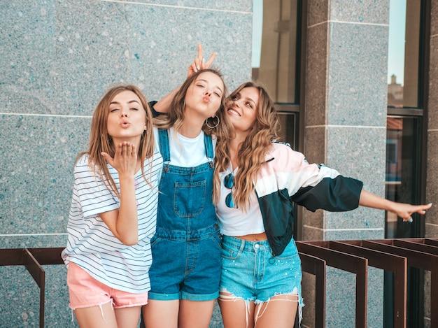 Ritratto di tre giovani belle ragazze sorridenti hipster in abiti estivi alla moda. donne spensierate sexy in posa sulla strada. divertimento di modelle positive. abbracciare e dare bacio d'aria