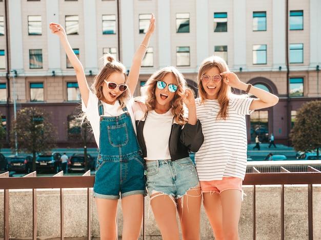 Ritratto di tre giovani belle ragazze sorridenti hipster in abiti estivi alla moda. donne spensierate sexy in posa sulla strada. modelli positivi che si divertono in occhiali da sole. mani che sollevano