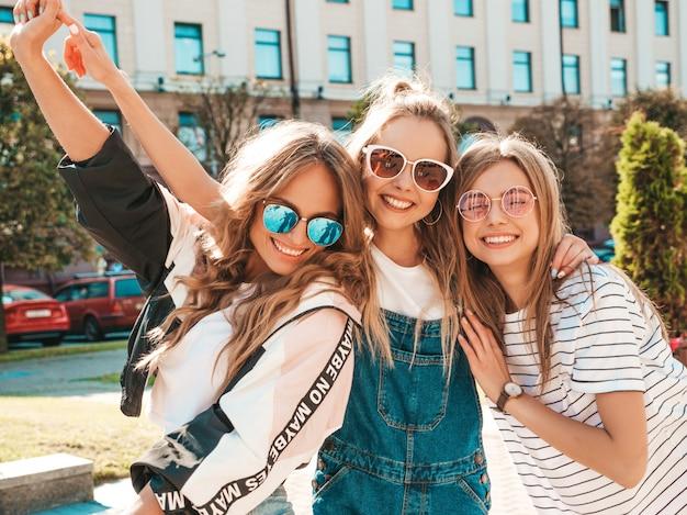 Ritratto di tre giovani belle ragazze sorridenti hipster in abiti estivi alla moda. donne spensierate sexy in posa sulla strada. modelli positivi che si divertono in occhiali da sole
