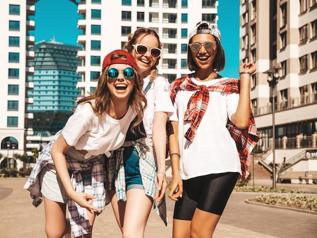 Ritratto di tre giovani belle ragazze sorridenti hipster in abiti estivi alla moda
