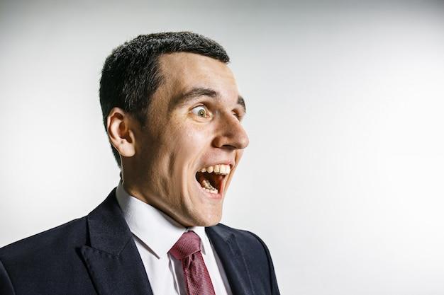 Ritratto di tre quarti di un uomo d'affari con la faccia sorpresa e sorridente. professionista fiducioso con uno sguardo penetrante in primo piano nella fotocamera.