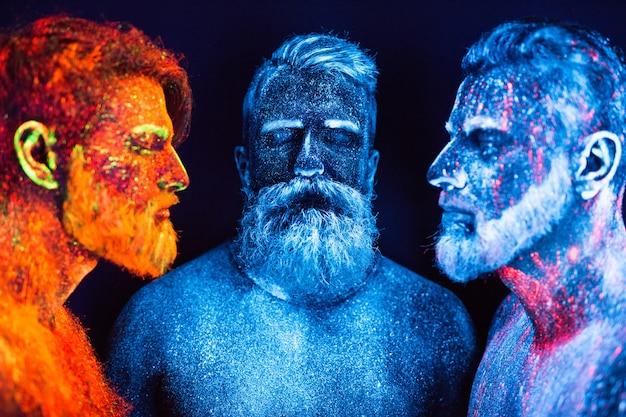 Ritratto di tre uomini barbuti dipinti con polveri fluorescenti.