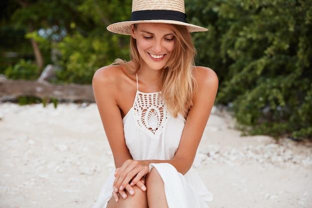 Ritratto di turista femminile timido felice ricreare ai tropici, indossa un cappello di paglia alla moda, si siede sulla sabbia, fa il bagno al sole, gode di aria fresca e tempo soleggiato. donna sorridente felice che è di buon umore come resti