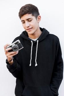 Ritratto di un adolescente che esamina macchina fotografica d'annata che sta contro il fondo bianco