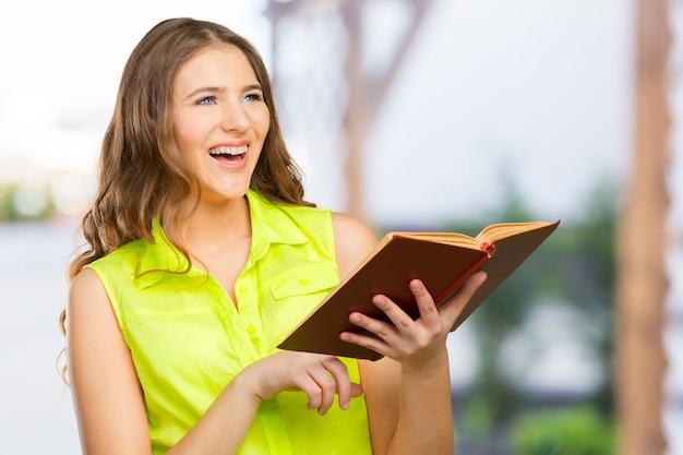 Ritratto di un adolescente femminile allegro con un libro