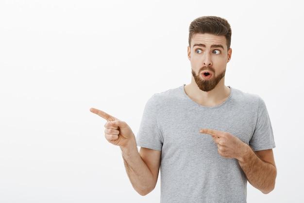 Ritratto di un affascinante modello maschio curioso e stupito di bell'aspetto con la barba che tiene il respiro che piega le labbra in un suono wow che guarda e punta a sinistra verso l'acconciatura fresca che vuole lo stesso mentre si trova nel negozio di barbiere