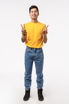 Ritratto di un affascinante ragazzo cinese verticale in maglietta gialla, jeans, che mostra il segno di pace e sorridere felice, esprimere positività, divertirsi, stare intrattenuto e gioioso, muro bianco