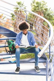 Ritratto di un allievo maschio che si siede sulla scala blu che legge il libro all'aperto