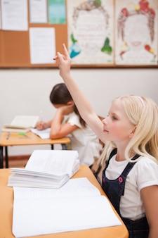 Ritratto di un alunno alzando la mano