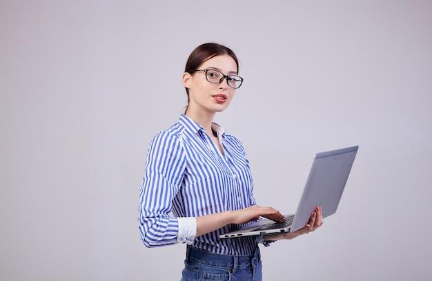 Ritratto di un amministratore femminile in una camicia bianco-blu a strisce con gli occhiali e un computer portatile su grigio. dipendente dell'anno, signora d'affari. copia spazio.