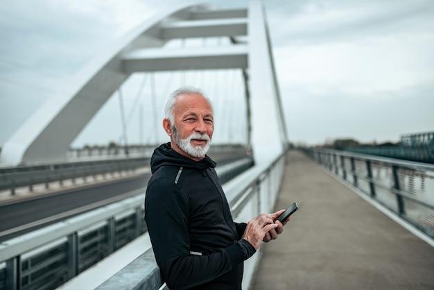 Ritratto di un anziano nel messaggio di testo degli abiti sportivi all'aperto, sul ponte della città.
