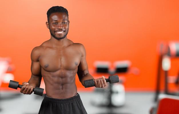 Ritratto di un atleta afroamericano a petto nudo isolato