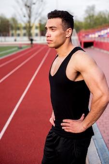 Ritratto di un atleta maschio sicuro che sta sulla pista corrente