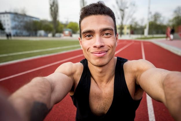 Ritratto di un atleta maschio sorridente sulla pista di corsa che prende selfie