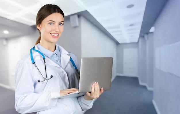 Ritratto di un attraente giovane dottoressa in camice bianco