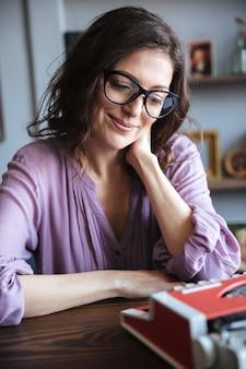 Ritratto di un'autrice sorridente matura che si siede allo scrittorio