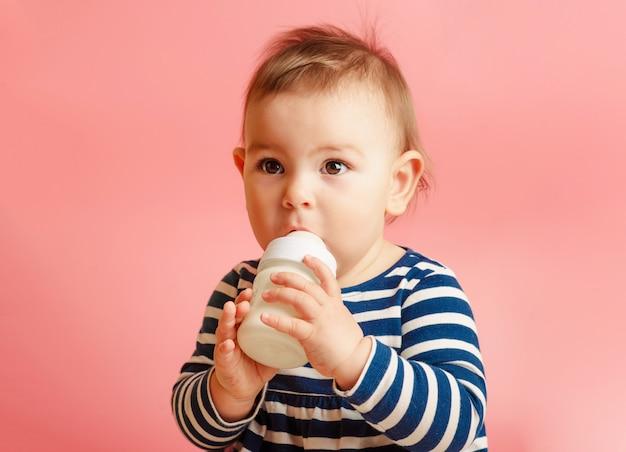 Ritratto di un bambino carino bere latte dalla bottiglia