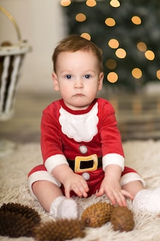 Ritratto di un bambino carino che gioca sul pavimento con coni per decorare l'albero di natale, vicino all'albero di natale e scatole con regali di natale, buon natale e buone feste,