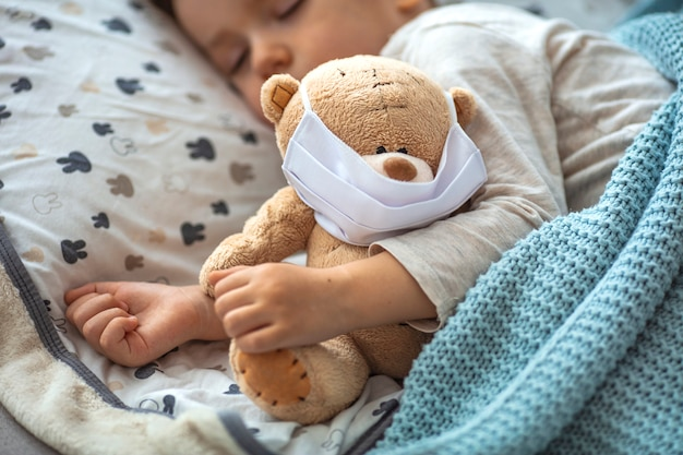 Ritratto di un bambino che dorme e orsacchiotto utilizzando maschere d'aria. bambino in casa in quarantena dormendo.