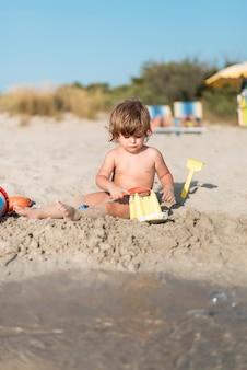 Ritratto di un bambino che fa un castello di sabbia