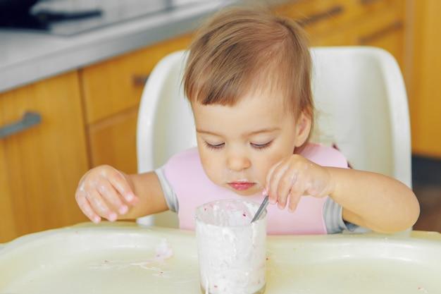 Ritratto di un bambino che mangia pappe con il suo cucchiaio.