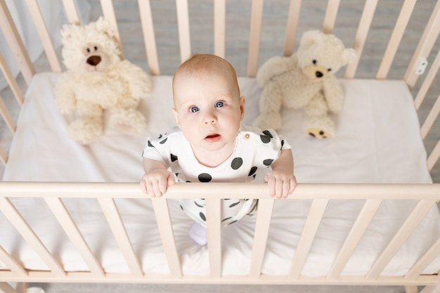 Ritratto di un bambino di 8 mesi in piedi in una culla con giocattoli in pigiama in una luminosa camera per bambini e guardando la telecamera