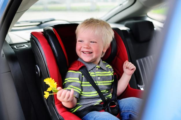 Ritratto di un bambino di un ragazzo con i capelli biondi in seggiolino auto per bambini.