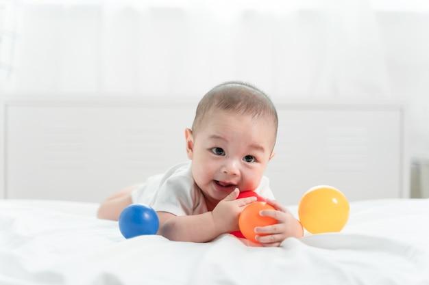 Ritratto di un bambino strisciante sul letto nella sua stanza e giocare a palla giocattolo, adorabile bambino in camera da letto soleggiata bianca.