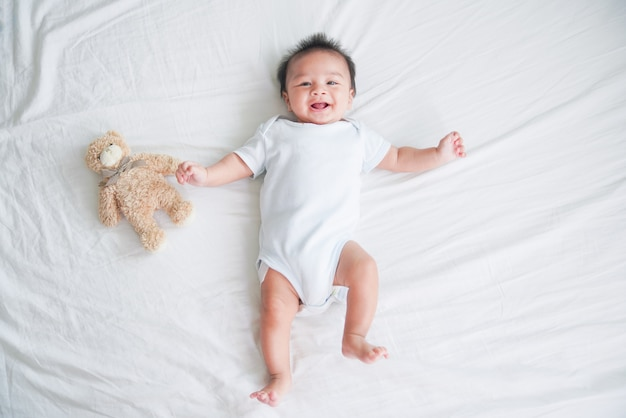 Ritratto di un bambino strisciare sul letto nella sua stanza, neonato rilassante nel letto