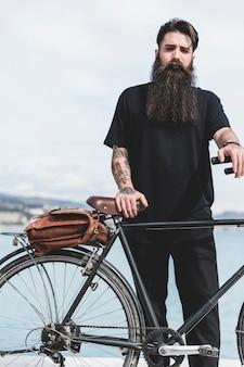 Ritratto di un bel giovane con la sua bicicletta