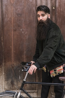 Ritratto di un bel giovane con lunga barba in piedi con la sua bicicletta