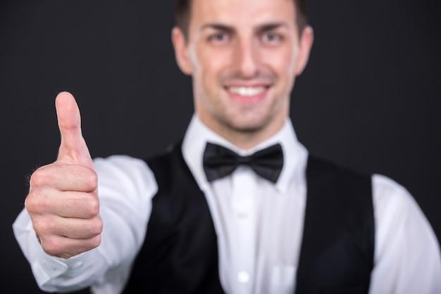 Ritratto di un bel giovane uomo sorridente in una tuta.