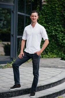 Ritratto di un bel uomo alto in una camicia bianca sulla strada.
