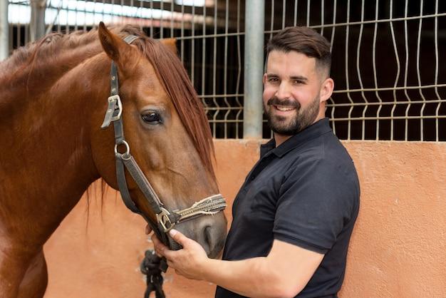Ritratto di un bell'uomo con il suo cavallo in piedi presso la scuderia