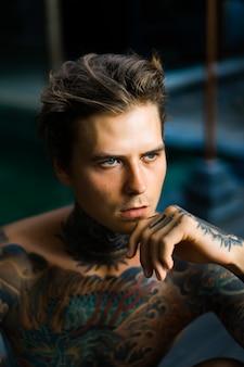 Ritratto di un bell'uomo in tatuaggi