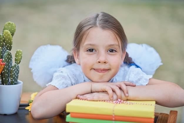 Ritratto di un bellissimo giovane di prima elementare seduto a una scrivania sul parco in autunno sfondo.
