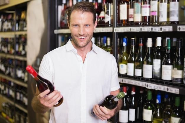 Ritratto di un bello sorridente che mostra una bottiglia di vino