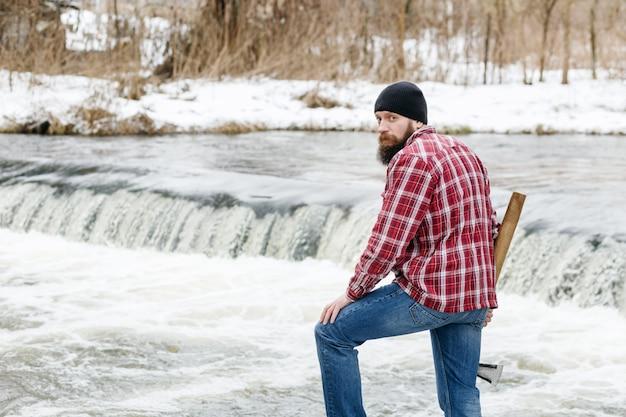 Ritratto di un boscaiolo con un'ascia sullo sfondo del fiume in primavera