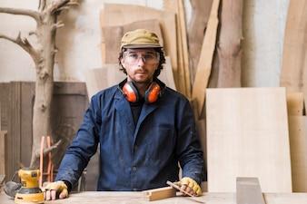 Ritratto di un carpentiere maschio che indossa gli occhiali di protezione che stanno dietro il banco da lavoro