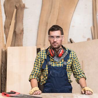 Ritratto di un carpentiere maschio che indossa il difensore per l'orecchio intorno al suo collo che guarda l'obbiettivo