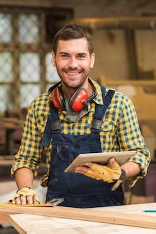 Ritratto di un carpentiere maschio sorridente che tiene compressa digitale a disposizione che esamina macchina fotografica