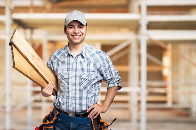 Ritratto di un carpentiere sorridente che tiene le plance di legno in un cantiere
