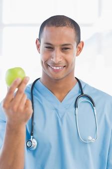Ritratto di un chirurgo sorridente che tiene una mela
