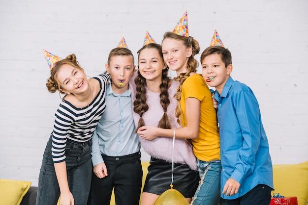Ritratto di un compleanno sorridente ragazza adolescente in posa con i suoi amici che indossa cappello di partito