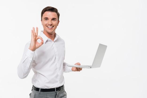 Ritratto di un computer portatile bello sorridente della tenuta dell'uomo