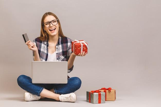 Ritratto di un computer portatile emozionante della tenuta della ragazza casuale e carta di credito mentre sedendosi su un pavimento con la pila di contenitori di regalo