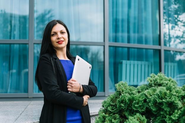 Ritratto di un computer portatile sorridente della tenuta della donna di affari davanti a costruzione di vetro