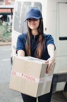 Ritratto di un corriere femminile sorridente con scatola di cartone